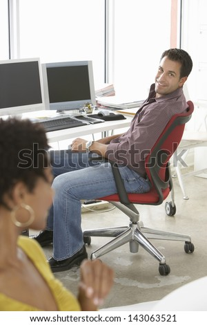 Happy businessman sitting on office chair with female colleague in foreground - stock photo