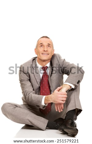 Happy businessman sitting on the floor looking up.