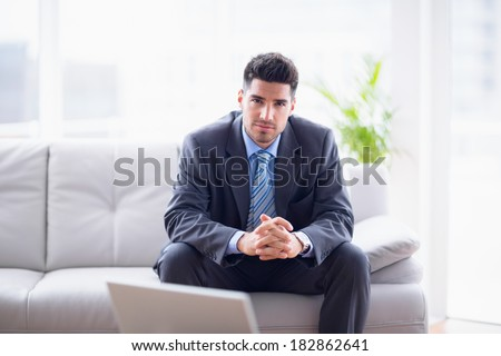 Happy businessman sitting on the sofa looking at camera in the office - stock photo