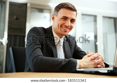 Happy businessman sitting with laptop at office - stock photo