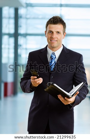 Happy businessman smiling at office lobby. - stock photo
