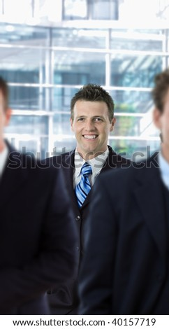 Happy businessman standing behind other businesspeople, in front of office building. - stock photo