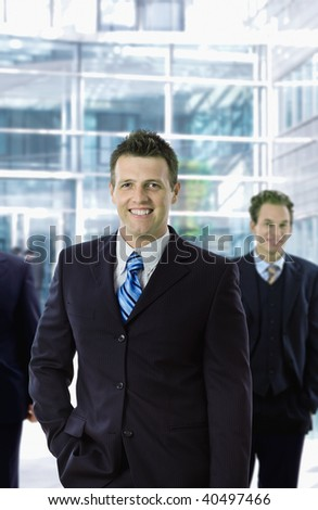 Happy businessman standing in front of office building, smiling. - stock photo