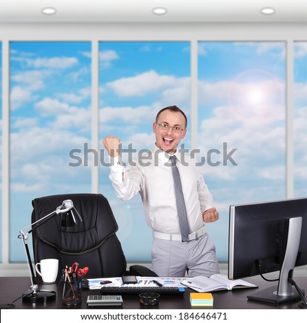 happy businessman standing in office with big window - stock photo