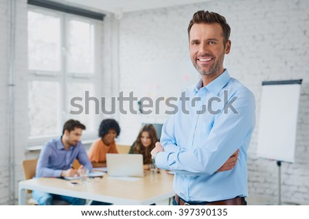 Happy businessman standing in the office with coworkers in the background working by the desk