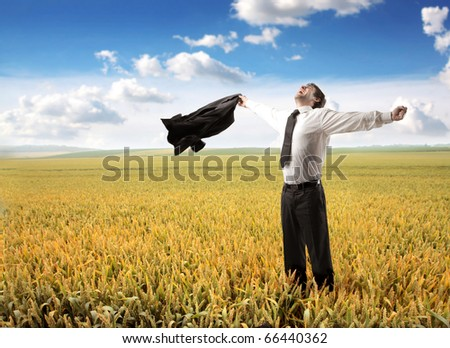 Happy businessman standing on a wheat field - stock photo