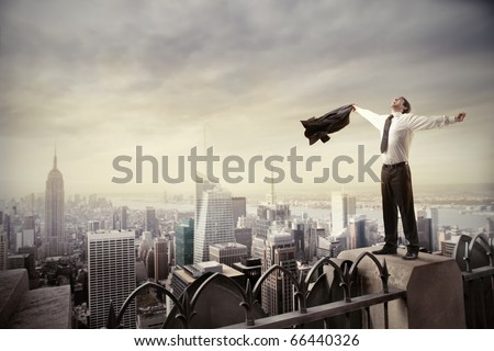 Happy businessman standing on the rooftop of a skyscraper over a cityscape - stock photo