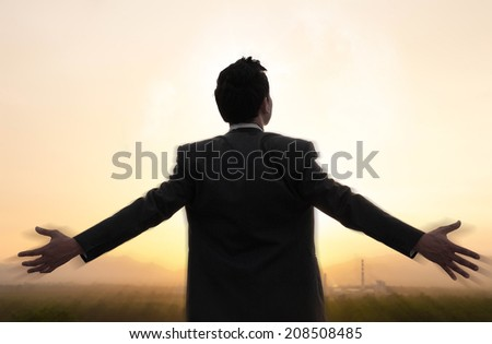 happy businessman standing over factory before the sunset - stock photo