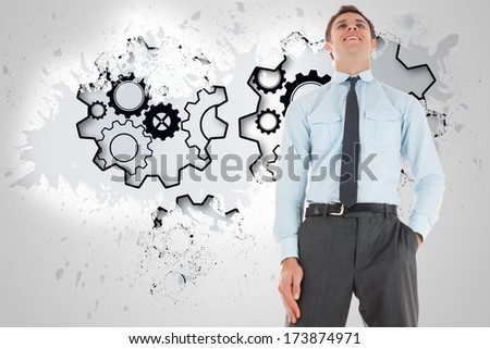 Happy businessman standing with hand in pocket against cityscape on the horizon - stock photo