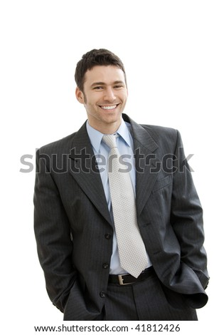 Happy businessman standing with hands in pocket, looking at camera, smiling. Isolated on white background.