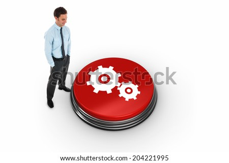 Happy businessman standing with hands in pockets against cog and wheel - stock photo