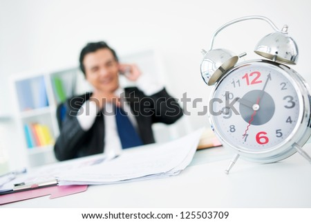 Happy businessman talking by the phone in his office while time ticking away on the clock - stock photo