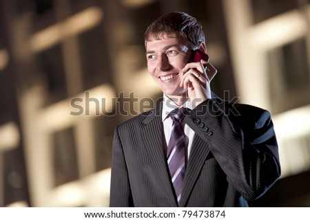 happy businessman talking on cell phone at night city in the background - stock photo