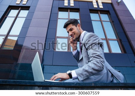 Happy businessman talking on the phone and using laptop outdoors - stock photo