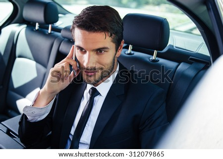 Happy businessman talking on the phone in car - stock photo