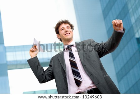 Happy businessman throwing paper airplane.