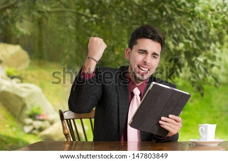 Happy businessman using his tablet in the house - stock photo