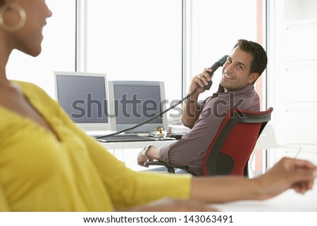 Happy businessman using landline phone while looking at female colleague - stock photo