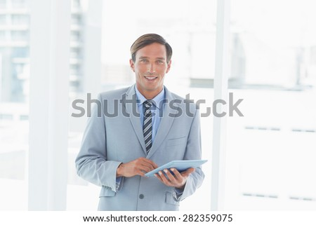 happy businessman using tablet pc in office - stock photo