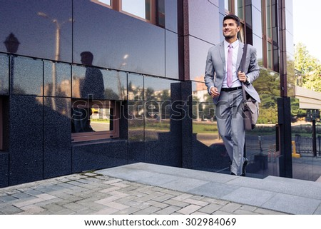 Happy businessman walking on stairs outdoors - stock photo