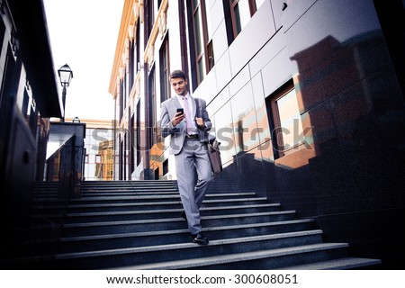 Happy businessman walking on the stairs and using smartphone outdoors - stock photo