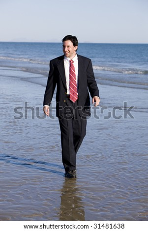 Happy Businessman Walking the Beach - stock photo