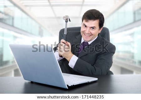 happy businessman with a hammer smashing a laptop, at the office - stock photo