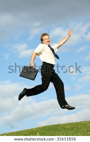 happy businessman with bag jumping in the air - stock photo