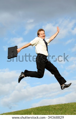 happy businessman with bag jumps in the air - stock photo