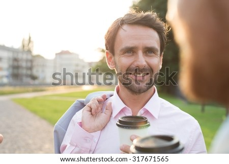 Happy businessman with colleague at park on sunny day - stock photo