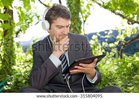 happy businessman with digital tablet and headphones, outdoors - stock photo