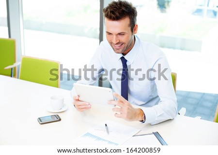 Happy businessman with digital tablet sitting at desk in the office