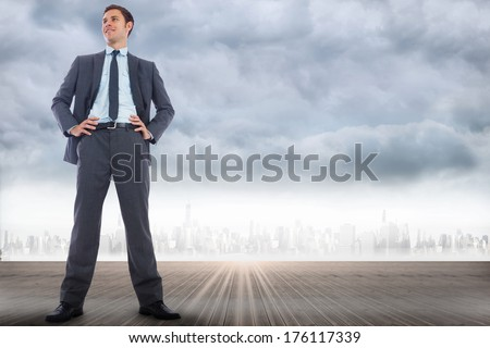 Happy businessman with hands on hips against city on the horizon