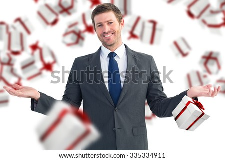 Happy businessman with hands out against white and red gift box - stock photo