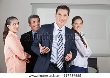 Happy businessman with his team in the office - stock photo