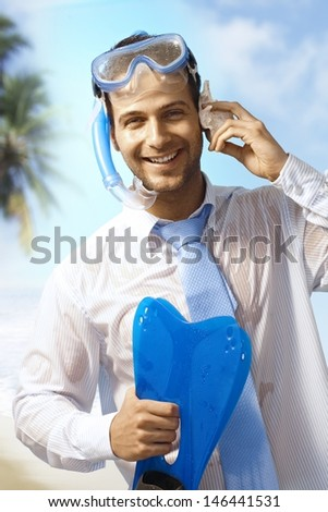 Happy businessman with scuba-diving equipments enjoying summer holiday, pretending to talking on mobile phone. - stock photo