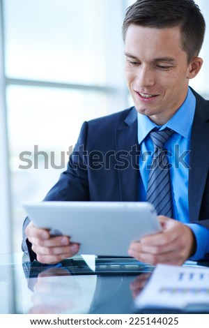 Happy businessman with touchpad networking in office - stock photo