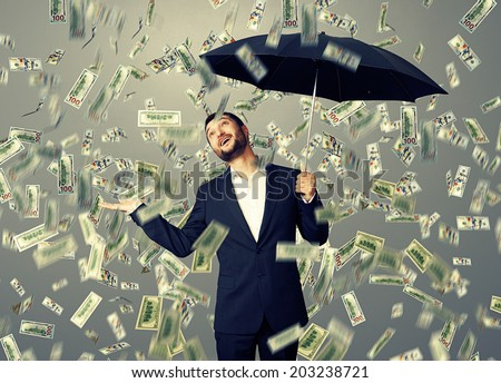 happy businessman with umbrella standing under money rain and looking up - stock photo