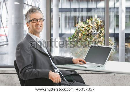 Happy businessman wokring on laptop computer at office desk, smiling.