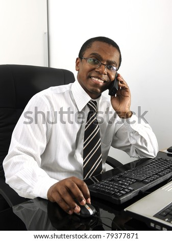 Happy businessman working at desk smiling - stock photo