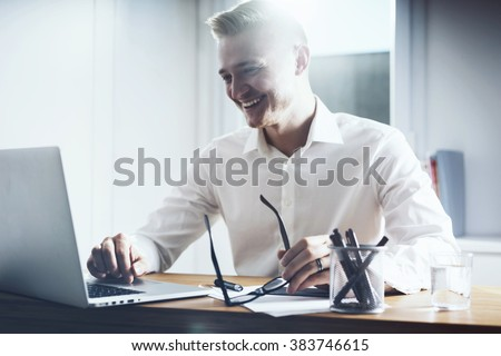 Happy businessman working at his office with laptop. Young smiling man sitting at his workplace with notebook computer and holding glasses in hand - stock photo