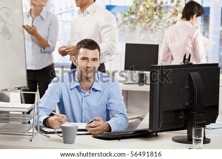 Happy businessman working in office, sitting at desk, writing notes to personal organizer.
