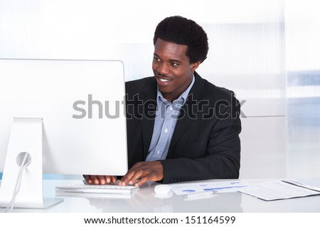 Happy Businessman Working On Computer In Office - stock photo