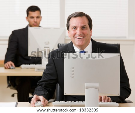 Happy businessman working on computer with co-worker in background