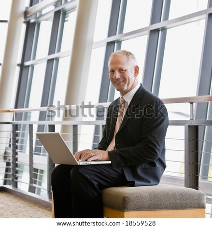 Happy businessman working on laptop in office lobby - stock photo