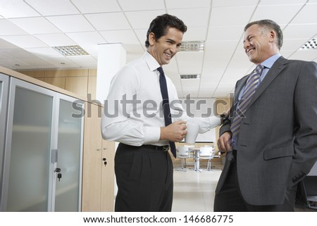 Happy businessmen communicating while standing in office - stock photo