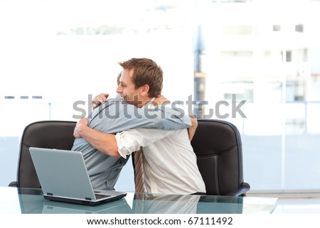 Happy businessmen congratulating each other on a success sitting at a table in the office - stock photo