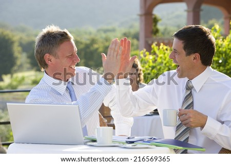 Happy businessmen giving high five and drinking coffee at caf�½ - stock photo