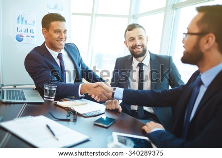 Happy businessmen handshaking after negotiation in office - stock photo