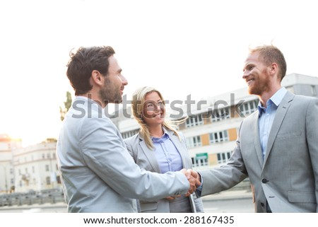 Happy businessmen shaking hands in city against clear sky